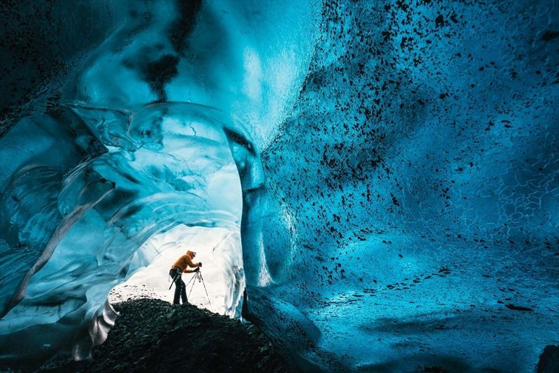 Wednesday 25th November 2015, Vatnajökull national park, Iceland: Photographer Mikael Buck with assistance from renowned local Icelandic guide Einar Runar Sigurdsson, explored the frozen world of Vatnajökull glacier in Iceland using Sony's world first back-illuminated full-frame sensor – which features in the α7R II camera. His images were taken without use of a tripod or any image stitching techniques in photoshop. This was made possible through Sony's new sensor technology, allowing incredibly detailed low-light hand held photography. Previously images this detailed would have required carrying bulky equipment to the caves, some of which can require hiking and climbing over a glacier for up to two hours to to access.  This picture: Inside the 'ABC cave' - which stands for Amazing Blue Cave.  Guide Einar Runar Sigurdsson is seen taking a photo at the entrance to the cave  PR Handout - editorial usage only. Photographer's details not to be removed from metadata or byline.  For further information please contact Rochelle Collison at Hope & Glory PR on 020 7014 5306 or rochelle.collison@hopeandglorypr.com  Copyright: © Mikael Buck / Sony 07828 201 042 / mikaelbuck@gmail.com